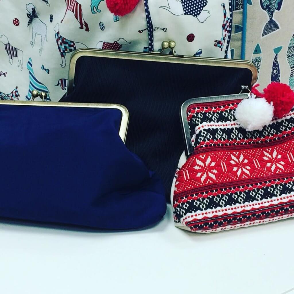Three clutch bags in blue, red and black.