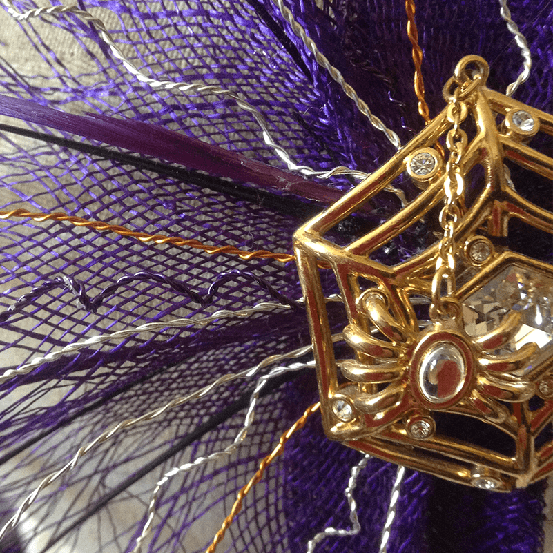 A spider themed head piece in purple and gold.