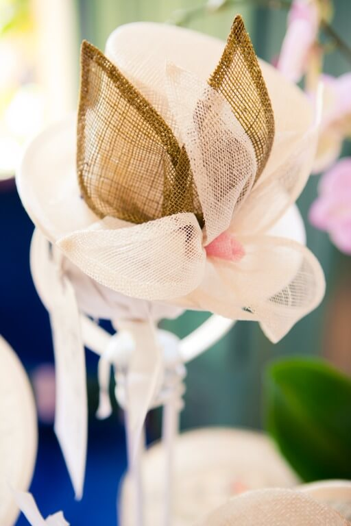 White and gold hat made in sinamay.